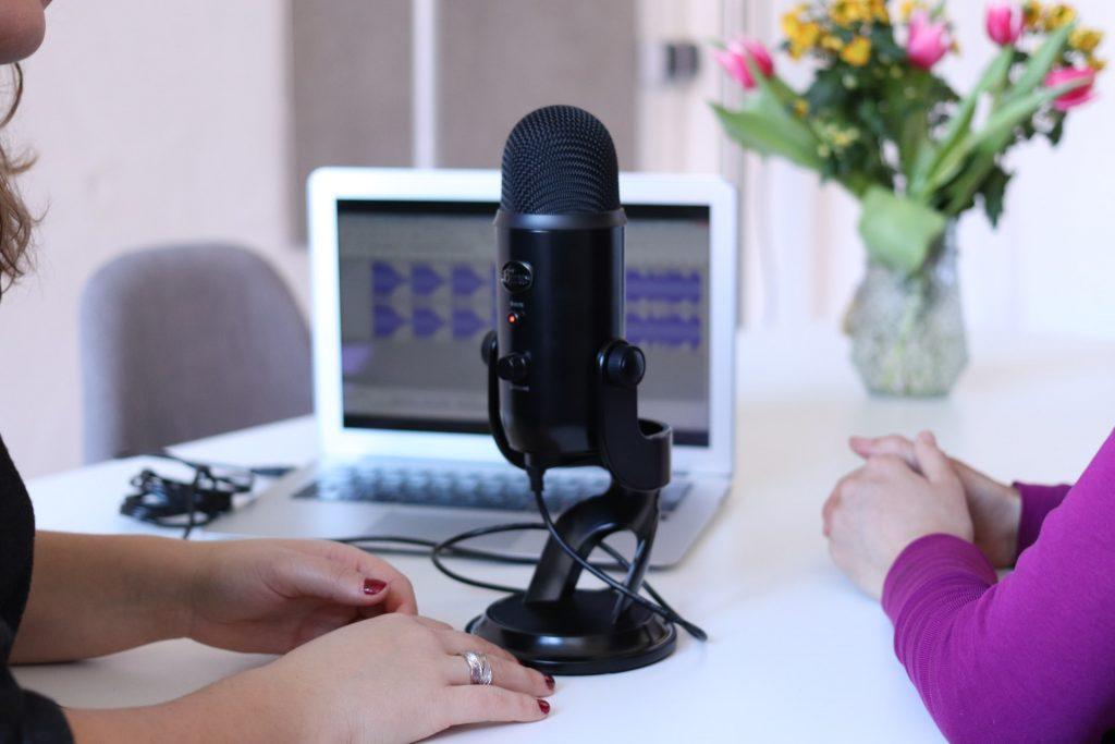 Deux personnes autour d'un micro enregistre un podcast pour une stratégie de content marketing